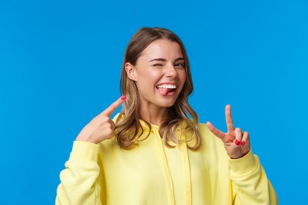 Close-up portret beztroskiej, entuzjastycznej blond dziewczyny w żółtej bluzie z kapturem, z przekłutym uchem, pokazującym język i mrugającym radośnie, wskazując się, wykonując gest pokoju,