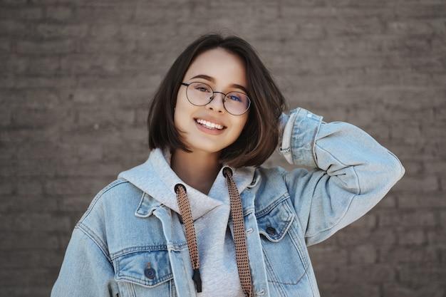 Close-up portret beztroskiej uroczej kobiety w okularach idącej z dziewczyną na zakupy spożywcze, dotykającej radośnie głowy i uśmiechającej się kamery, stojącej przy ceglanej ścianie, wyrażającej beztroskie uczucia.