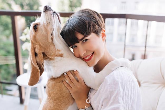 Close-up portret błogiej dziewczyny z szarymi oczami pozuje z radosnym uśmiechem, podczas gdy jej pies beagle patrząc w górę