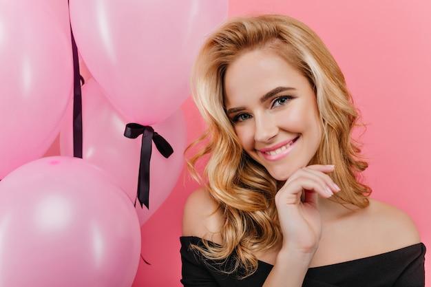 Close-up portret błogiej jasnowłosej dziewczyny ze szczerym uśmiechem stwarzających w jej urodziny. niebieskooka dama z blond kręconymi włosami oglądająca sesję zdjęciową z balonów i śmiejąca się.