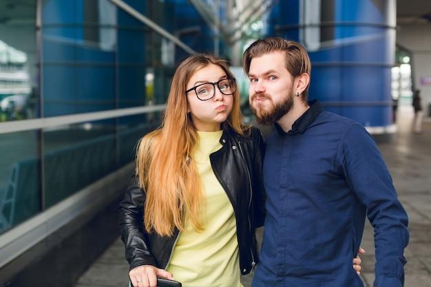 Close-up portret cute para stojących na zewnątrz na lotnisku. ma długie włosy, okulary, żółty sweter, kurtkę. nosi czarną koszulę, brodę. przytulają się i małpują do kamery.