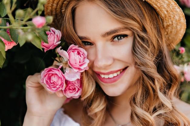Close-up portret czarującej dziewczyny z błyszczącymi oczami z kwiatem. spektakularna blondynka w kapeluszu trzyma różową różę i uśmiecha się.
