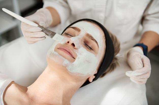 Close-up portret dłoni kosmetyczki nakładającej maseczkę kosmetyczną na twarz młodej kobiety z idealnie czystą skórą za pomocą pędzla. profesjonalna koncepcja pielęgnacji skóry w nowoczesnych salonach kosmetycznych spa