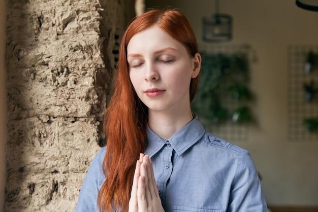 Close-up portret długowłosy rudowłosy kobieta pozuje do portretu z zamkniętymi oczami i założonymi rękami przed twarzą w postawie modlitwy lub medytacji