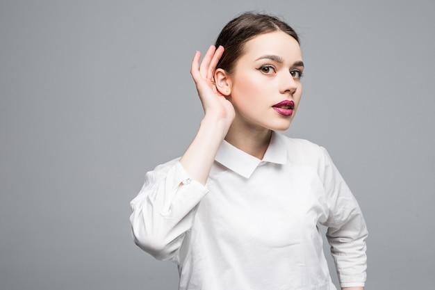 Close-up portret dziewczyny słuchającej plotek i słysząc coś ważnego na białej ścianie