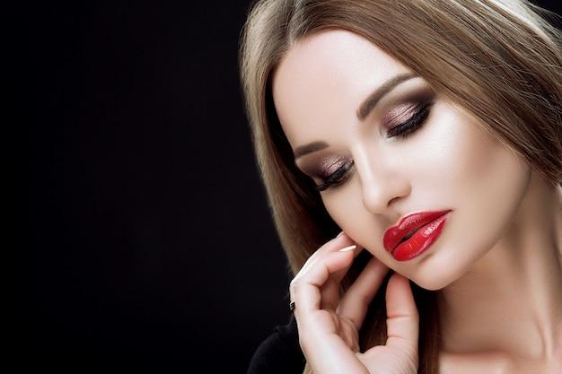 Close-up portret eleganckiej kobiety z jasnym makijażem, czerwonymi ustami, długimi rzęsami, prostymi długimi włosami, idealnymi brwiami, manicure.