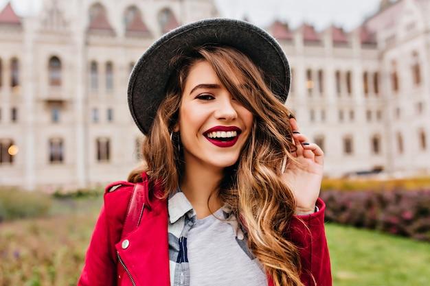 Close-up portret fascynującej białej modelki pozuje z radosnym uśmiechem na ścianie architektury