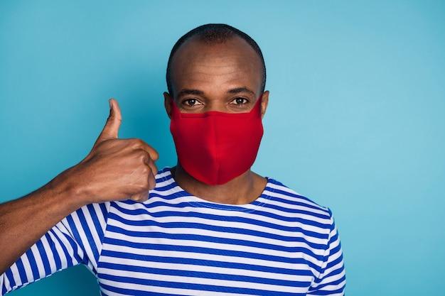 Close-up portret jego ładnego zdrowego faceta ubrany w czerwoną bawełnianą tekstylną maskę bezpieczeństwa wielokrotnego użytku pokazujący thumbup stop mers cov zapobieganie chorobom grypy na białym tle nad niebieskim kolorem tła