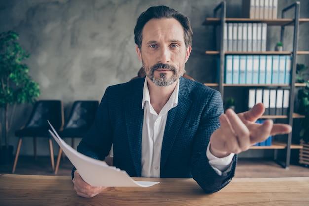 Close-up portret jego miłego atrakcyjnego mężczyzny wykwalifikowanego eksperta czytającego omawiającego papierkową robotę zatrudnianie utalentowanych pracowników budowanie zespołu oferta odpowiedzialność nowoczesny beton przemysłowy stanowisko pracy