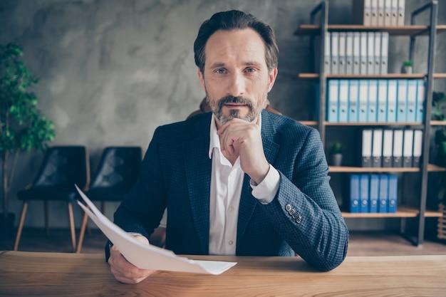 Close-up portret jego miłego atrakcyjnego mężczyzny wykwalifikowanego profesjonalnego eksperta czytającego dokument cv zatrudniającego utalentowanych pracowników to rozwój firmy na nowoczesnym betonowym miejscu pracy przemysłowej
