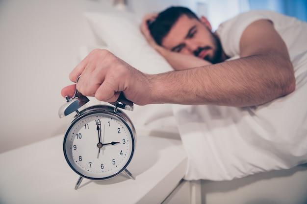Close-up portret jego miłego atrakcyjnego podrażnionego zmęczonego faceta leżącego na łóżku trzymającego w ręku budzik cierpiącego na choroby w nocy późnym wieczorem dom hotel biały pokój mieszkanie dom