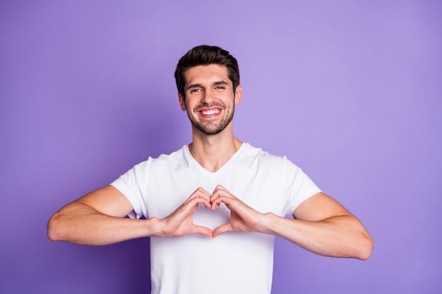 Close-up portret jego miłego atrakcyjnego uroczego wesołego wesołego brunetki pokazującego ręce gest kształt serca kocham cię na zawsze na fioletowym fioletowym fioletowym tle pastelowych kolorów