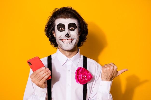 Close-up portret jego miły przystojny przerażający upiorny wesoły zadowolony facet za pomocą aplikacji gadżetowej 5g demonstrujący kopia przestrzeń reklama calavera na białym tle jasny żywy połysk żywy żółty kolor tła