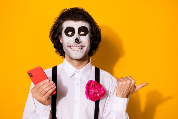 Close-up portret jego miły przystojny upiorny wesoły zadowolony facet za pomocą aplikacji urządzenia 5g smm pokazujący kopia przestrzeń porady calavera wygląd pomysł na białym tle jasny żywy połysk żywy żółty kolor tła