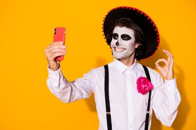 Close-up portret jego miły przystojny wesoły zadowolony upiorny facet caballero robi selfie calavera karnawał celebracja pokazując ok znak na białym tle jasny żywy połysk żywy żółty kolor tła