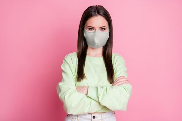 Close-up portret jej atrakcyjna treść prostowłosa dziewczyna nosząca bezpieczeństwo wielokrotnego użytku szara bawełniana maska tekstylna założonymi rękami zapobieganie zanieczyszczeniom na białym tle różowy pastelowy kolor tła