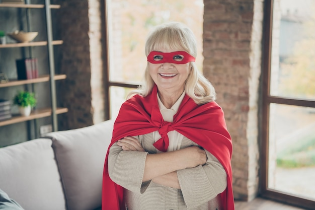 Close-up portret jej ładna, wesoła, wesoła, siwowłosa dama w czerwonym kostiumie super niania planeta ratuj służbę ratowniczą złożone ramię w industrialnym ceglanym poddaszu w nowoczesnym stylu