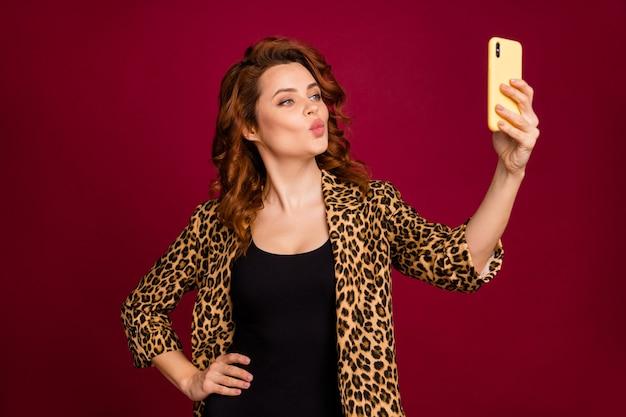 Close-up portret jej ładnej atrakcyjnej uroczej ładnej sympatycznej wesołej falistej dziewczyny biorącej robienie selfie wysyłanie pocałunku na białym tle na czerwony bordowy bordowy marsala kolor tła