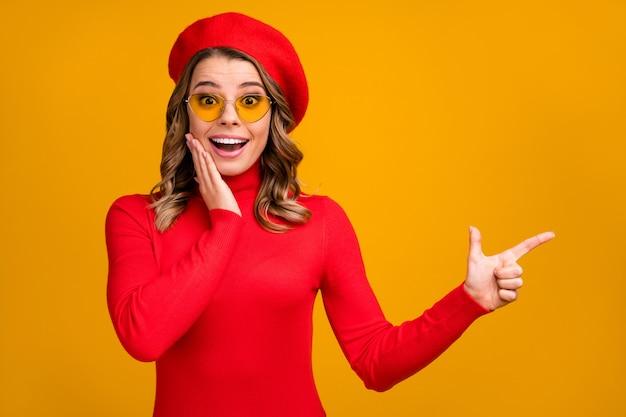 Close-up portret jej ładnie wyglądającej atrakcyjnej modnej wesołej zadowolonej zdumionej falistej dziewczyny pokazującej miejsce na kopię reklamową na jasnym żywym połysku żywy żółty kolor tła