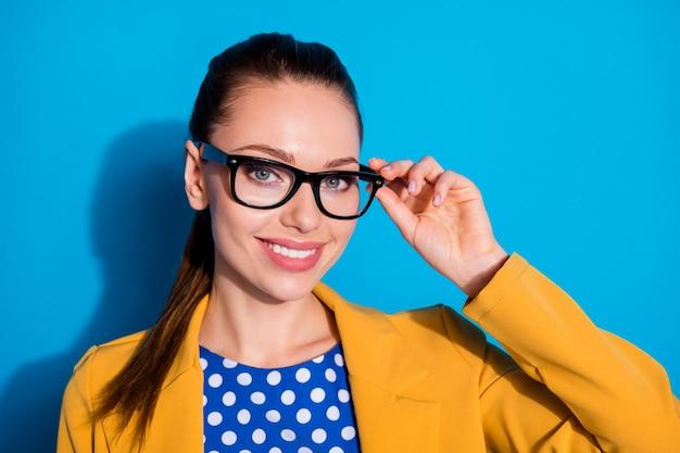 Close-up portret jej ładnie wyglądającej atrakcyjnej uroczej całkiem słodkiej wesołej inteligentnej mądrej pani dotykającej okularów odizolowanych nad jasnym żywym połyskiem żywym niebieskim kolorem tła
