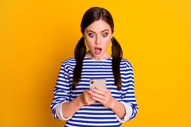 Close-up portret jej ona ładna atrakcyjna całkiem urocza zdumiona zmartwiona brązowowłosa dziewczyna za pomocą urządzenia przeglądającego fałszywe wiadomości na białym tle jasny żywy połysk żywy żółty kolor tła