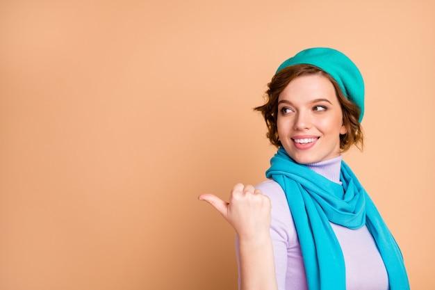 Close-up portret jej ona ładna atrakcyjna całkiem wesoła dziewczyna wskazując kciukiem na bok wybierz wybór ogłoszenie ogłoszenie porady kopia puste puste miejsce miejsce na białym tle nad beżowym pastelowym kolorem tła