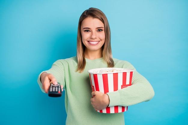Close-up portret jej ona ładna atrakcyjna śliczna całkiem wesoła wesoła zadowolona dziewczyna je kukurydza ogląda dobry program telewizyjny je kukurydza na białym tle na jasny żywy połysk żywy niebieski kolor tła