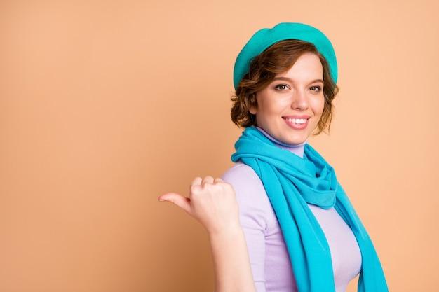 Close-up portret jej ona ładna atrakcyjna urocza całkiem pewna siebie wesoła wesoła dziewczyna wskazując kciukiem na bok wybierz wybór reklama ogłoszenie decyzja kopia przestrzeń na białym tle nad beżowym pastelowym kolorem tła