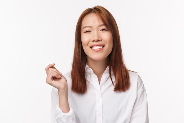 Close-up portret kobieca uśmiechnięta azjatycka dziewczyna w białej koszuli, patrząc w kamerę radosną i entuzjastyczną, rozmawiając z przyjacielem, wyrażaj pozytywne emocje z radosnym wyrazem twarzy,