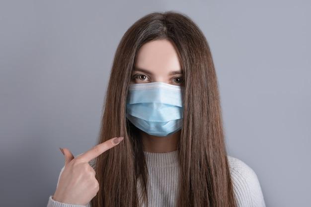 Close-up portret kobiety, dziewczynki, nastolatka, jej, ładna atrakcyjna, kochana, urocza urocza, urocza dziewczyna z długimi ciemnymi włosami nosi biały sweter ochrona grypy zimna maska medyczna na twarz na szarym