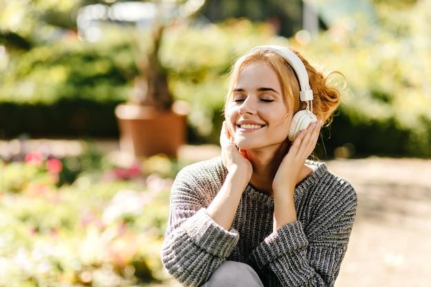 Close-up portret kobiety, słuchającej muzyki w dobrym nastroju, ubrana w szary sweter z dzianiny.