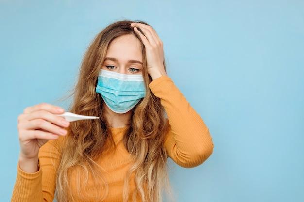 Close-up portret kobiety w masce medycznej na twarzy z podejrzeniem koronawirusa i ramię z wyciągniętym termometrem. covid-2019. kobieta.