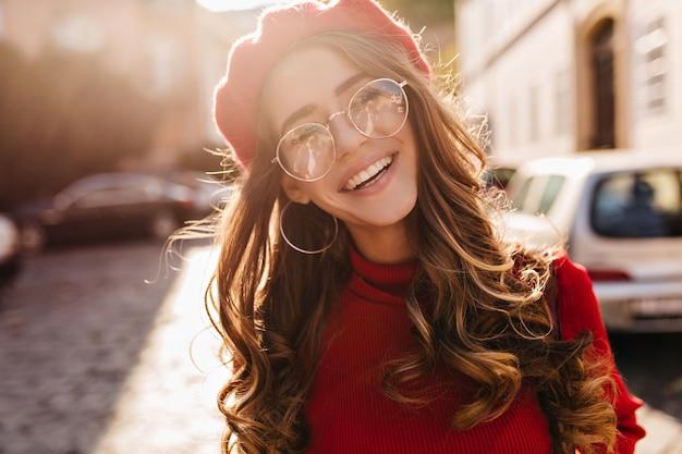 Close-up portret kochanej francuskiej dziewczyny z elegancką kręconą fryzurą, patrząc na kamery i śmiejąc się