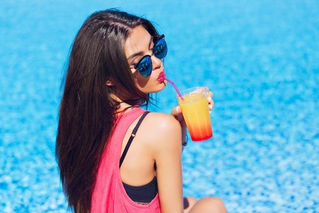 Close-up portret ładna brunetka dziewczyna z długimi włosami siedzi na tle wody. ona pije koktajl przez słomkę. widok z tyłu.
