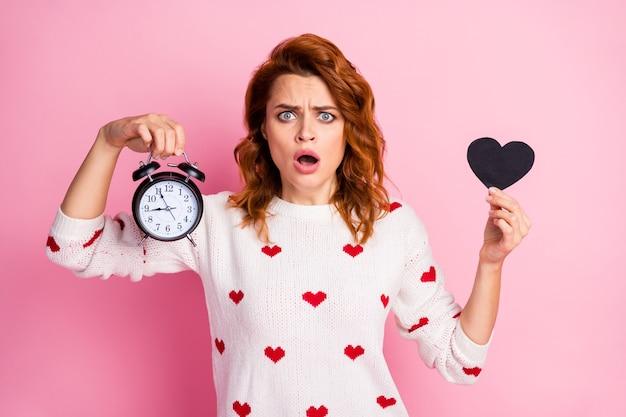 Close-up portret ładne atrakcyjne ładne słodkie piękne zmartwiona nerwowa dziewczyna trzyma w ręku czarne serce dzwon zegar kłopoty stres