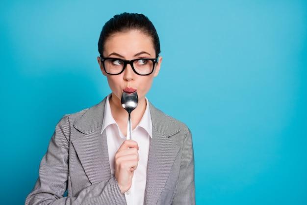 Close-up portret ładnej atrakcyjnej głodnej pani liżącej łyżkę liczącą kalorie dietetyczne izolowane na jasnym niebieskim tle koloru