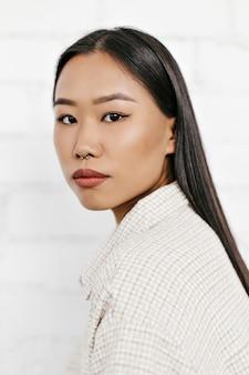 Close-up portret ładnej brunetki w beżowej kurtce w kratę patrzy w kamerę i pozuje na białej ścianie z cegły