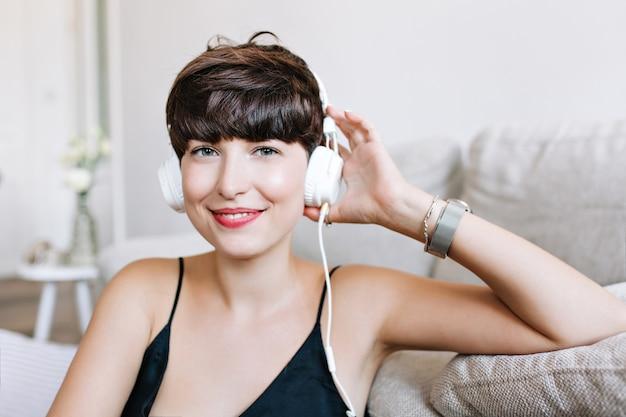 Close-up portret lekko opalonej, roześmianej dziewczyny z szarymi oczami słuchających muzyki