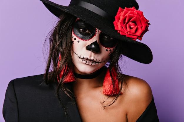 Close-up portret meksykańskiej damy, która wykonała jasny makijaż na dzień wszystkich zmarłych. kobieta z czerwonymi akcesoriami pozuje na liliowej ścianie.