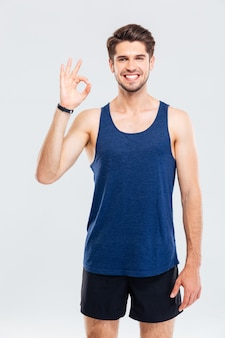 Close-up portret mężczyzny fitness pokazujący znak porządku na białym tle na szarym tle