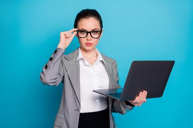 Close-up portret miłej, doświadczonej, wykwalifikowanej, inteligentnej, mądrej dziewczyny trzymającej w ręku laptopa dotykającego specyfikacji izolowanych na jasnym niebieskim tle koloru