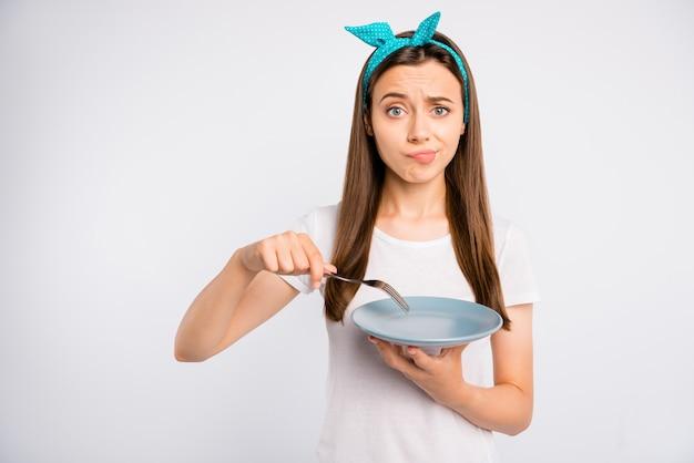 Close-up portret miły piękny rozczarowany dziewczyna trzyma w rękach pusty talerz widelec kara głód na białym tle