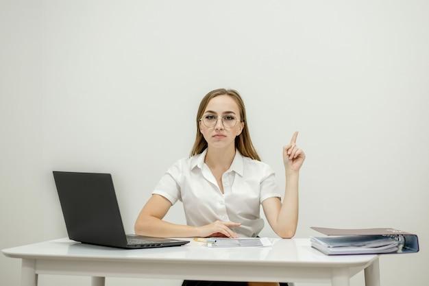 Close-up portret młodego kierownika biura pewnie kobiet w jej miejscu pracy, gotowy do robienia zadań biznesowych.