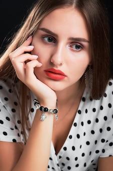 Close-up portret młodej dziewczyny z długimi włosami i czerwonymi ustami.