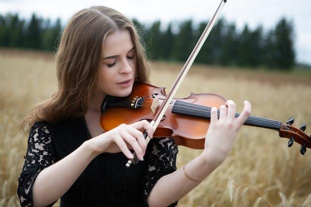 Close-up portret młodej kobiety z lekkim uśmiechem i spuszczonymi oczami, która gra na skrzypcach w polu pszenicy.