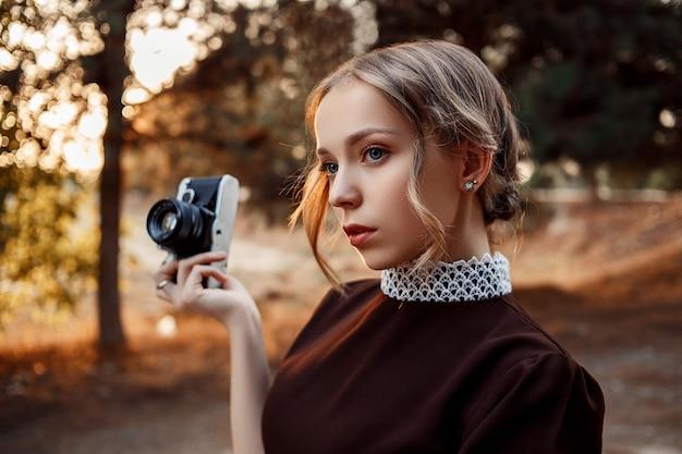 Close-up portret młodej pięknej dziewczyny w brązowej sukience w stylu retro z zabytkowym aparatem w dłoniach na opuszczonej drodze.