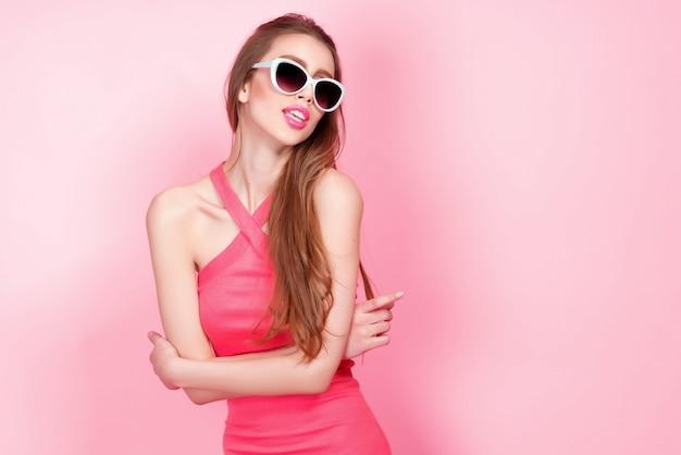 Close-up portret młodej pięknej szczupłej seksownej młodej kobiety w seksownej sukni z czerwonymi zmysłowymi ustami na różowych okularach przeciwsłonecznych. uśmiecha się i pozuje