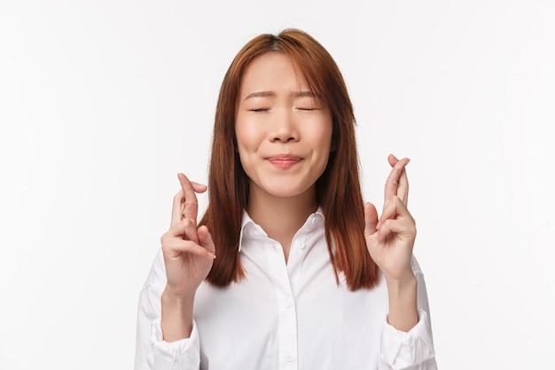 Close-up portret nadziei i podekscytowanej azjatyckiej kobiety, która chce awansować, zamyka oczy i błaga kciuki o powodzenie, błagając, przewidując cud, na białej ścianie
