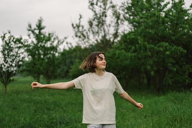 Close-up portret nastolatek dziewczyny. szczęśliwa wesoła nastoletnia dziewczyna z wyrazistą twarzą od spryskanych małych rozprysków wody lub ciepłego letniego deszczu na zewnątrz.