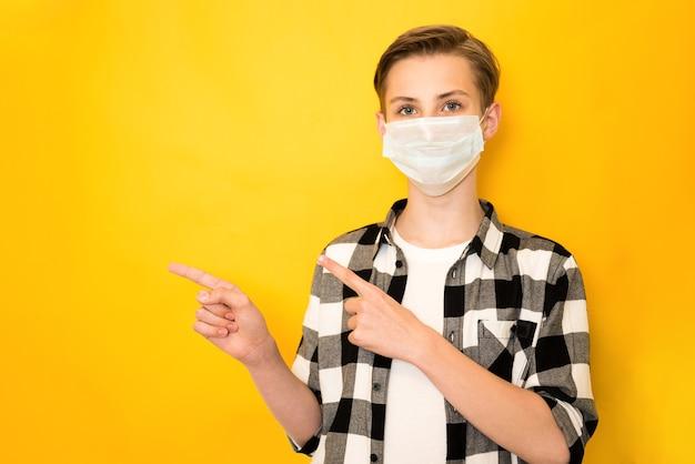 Close-up portret nastoletniego zdrowego chłopca zdrowego noszenia maski z gazy bezpieczeństwa pokazując miejsce na kopię na białym tle na żółtym tle
